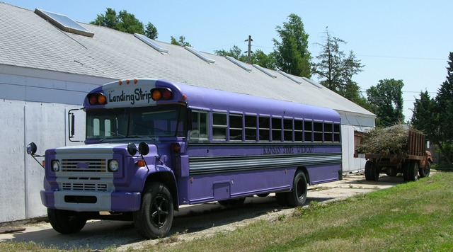 Purple schoolbus by shed with grain truck