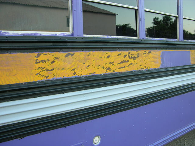 Purple paint stripped from schoolbus with fine wire wheel on angle grinder