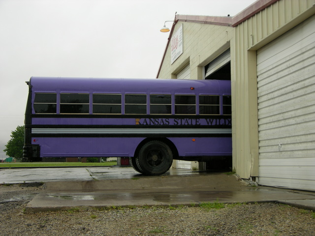 Purple schoolbus pulled into shop for engine cleaning