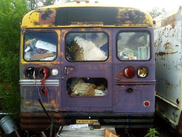 Rear end of Bluebird bus in junkyard