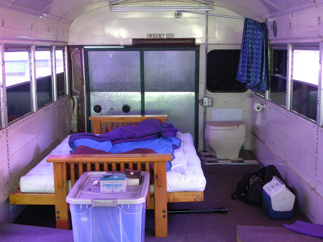 Rear interior of schoolbus RV with futon