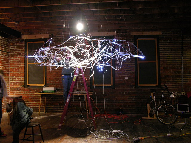 Lisa Rundstrom installing LEDs on Organic Energy Cloud exhibit